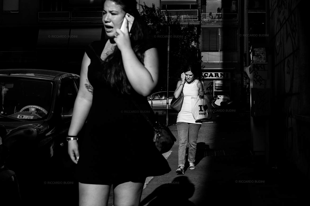 Girls talking on the phone on the street.