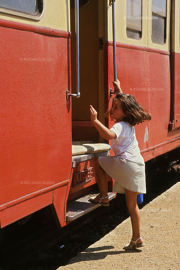 A little girl gets on the train. L'Île-Rousse, Corsica